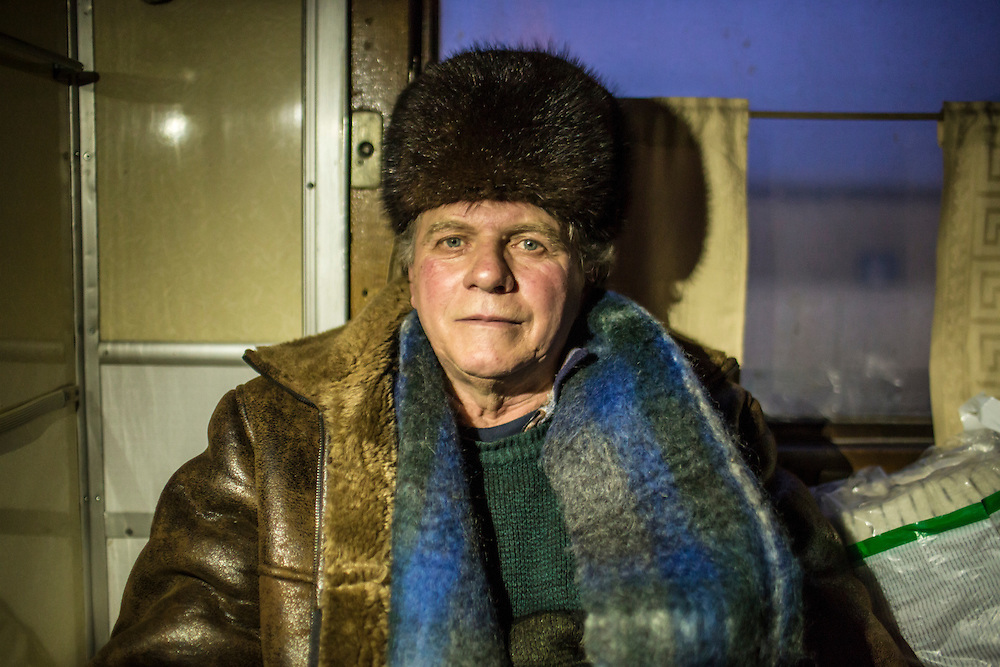 SLOVYANSK, UKRAINE - FEBRUARY 7, 2015: Vladimir Kovalo, 66, who was displaced by fighting in the town of Debaltseve, poses for a portrait inside a train in which he is being temporarily housed in Slovyansk, Ukraine. Many civilians have been evacuated from Debaltseve and brought to Slovyansk, where they are either given a free onward ticket or housed in the train or another facility until they can make further plans. CREDIT: Brendan Hoffman for The New York Times