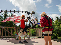 Adele Robertson gets help for her guides as she makes it to the first landing of Gunstock Mountain's Zipline Thursday afternoon.  (Karen Bobotas/for the Laconia Daily Sun)