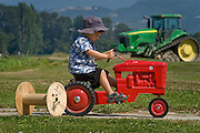 Skagit Valley, WA. farm boy pedaling toy tractor in field.