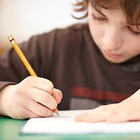 Study, young boy writing with a pencil