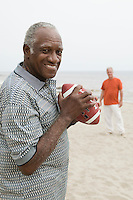 Two senior men playing american football on beach