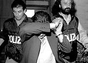 luogo : Napoli ( Questura ) - data : 04 ottobre 1993 - titolo : Manette<br /> ( Servizio inerente i fatti criminosi avvenuti in Campania e a Napoli nell'ultimo decennio )<br /> copyright Stefano Renna fotografia.<br /> Manette<br /> <br /> Le manette fanno parte della simbologia pi&ugrave; tetra  per un camorrista,  segno di sconfitta e di &ldquo;scuorno&rdquo;.  Per questo vengono spesso adoperate per nascondere il volto, nella vergogna e nella rabbia,  le manette ai polsi covano  vendette tremende, gi&agrave; pianificate  o sentenze di morte  gi&agrave; scritte per gli &ldquo;infami&rdquo;. <br /> Handcuffs <br /> <br /> Handcuffs are part of the gloomiest symbology  for a camorra man, a sign of defeat and shame.  That&rsquo;s why they often use them to hide their faces, in shame and anger. Handcuffs on their wrists, they prepare  a terrible revenge, already planned,  or death sentences  already written for &lsquo;traitors&rsquo;.<br /> <br /> VAI ALLE FOTO IN ARCHIVIO<br /> http://stefanorenna.photoshelter.com/gallery/03-MANETTE/G0000KWxrZcFd4XQ/C0000ujr_mqfrFyY