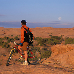 Moab, UT..Mountain biking on the Moab Slickrock Bike Trail.  Navajo Sandstone.  BLM land.  Full moon.