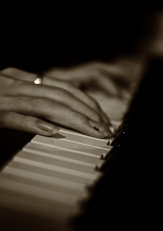 Fingers on the piano keys.