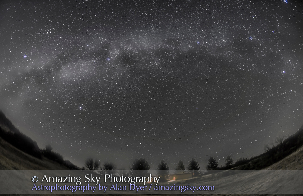 The arch of the Milky Way in the northern autumn and early winter sky, from Arizona on December 5, 2015. The Milky Way extends from Aquila to the left, in the southwest to Cassiopeia at top right, to Perseus and Auriga at far right, in the northeast. I shot this from the Quailway Cottage near Portal, Arizona, latitude +32&deg; N. The view is looking north toward the celestial pole. Polaris is just right of lower centre.<br />  <br /> This is a stack of 8 tracked exposures, each 3 minutes at f/2.8 with the 15mm lens and Canon 6D at ISO 1600, with the ground coming from one exposure to minimize blurring. The camera was on the iOptron Sky-Tracker. This version of the image has been processed to make the view better resemble what you see with the unaided eye, in a largely monochrome and softer view than the colourful and high-contrast views commonly presented in astrophotos. Even at that there is more fine structure present in the Milky Way than the unaided eye usually sees, though binoculars beging to reveal that smaller detail. I have left some colours in some stars and in the foreground of landscape scenes.