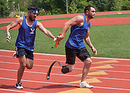 West Point, New York - Air Force's Daniel Crane, left, hands the baton to teammate Nicholas Dadgostar in the 400-meter relay at the 2014 Army Warrior Trials at the United States Military Academy Preparatory School on Tuesday, June 17, 2014.<br />
