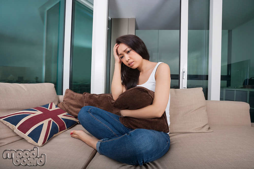 Full length of worried young woman sitting on sofa