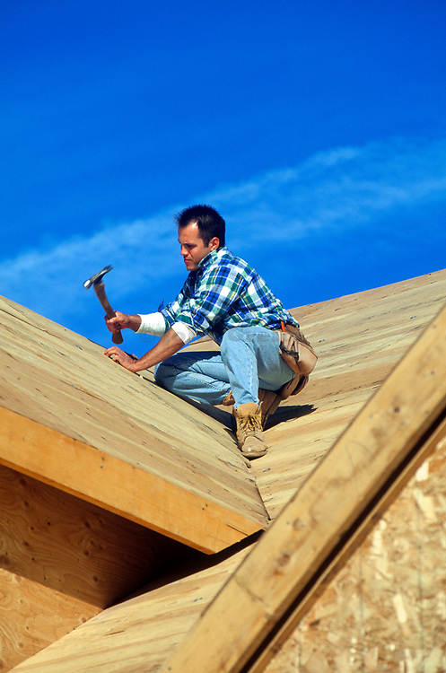 Construction worker hammering on the roof of a new house. MR