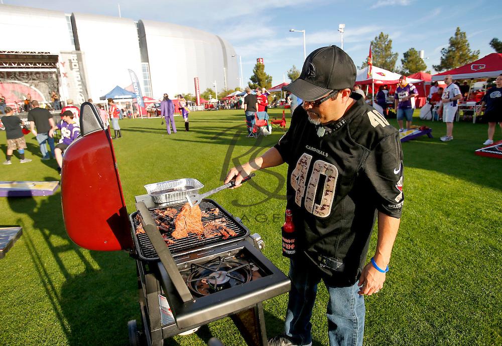 Michael Blea grills outside University of Phoenix Stadium prior to an NFL football game between the Arizona Cardinals and the Minnesota Vikings, Thursday, Dec. 10, 2015, in Glendale, Ariz. (AP Photo/Rick Scuteri)