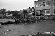 "Flooding at the Dodder..1986..26.08.1986..08.26.1986..28th August 1986..As a result of Hurricane Charly (Charlie) heavy overnight rainfall was the cause of severe flooding in the Donnybrook/Ballsbridge areas of Dublin. In a period of just 12 hours it was stated that 8 inches of rain had fallen. The Dodder,long regarded as a ""Flashy"" river, burst its banks and caused great hardship to families in the 300 or so homes which were flooded. Council workers and the Fire Brigades did their best to try and alleviate some of the problems by removing debris and pumping out some of the homes affected..Note: ""Flashy"" is a term given to a river which is prone to flooding as a result of heavy or sustained rainfall...With the threat of a high tide looming,picture shows workmen struggling to remove the debris from the watermain crossing the river at Ballsbridge,Dublin."