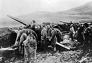 A Serbian heavy artillery battery, men standing in wet, muddy fortification, looking outwards in the same direction as the guns are pointing. Austro-Hungary invaded Serbia in July 1914.