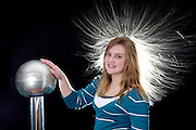 Girl placing her hand on a Van de Graaff electrostatic generator, a device that transmits excess electrons. Strands of the young woman's hair repel each other because they are similarly charged; the child's hairstyle displays electric field lines.