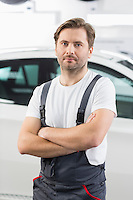 Portrait of confident male mechanic standing arms crossed in workshop