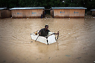 CLIENT: SAVE THE CHILDREN<br /> <br /> A boy uses a broken refrigerator to paddle around a flooded area in Leogane, Haiti, as Hurricane Tomas passes through.
