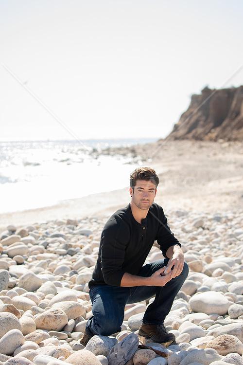 hot All American man kneeling on a rocky beach in Montauk, NY