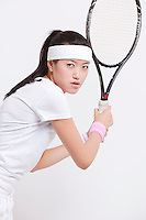 Portrait of young Asian woman holding tennis racket against white background