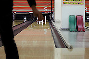 person throwing the ball in a bowling alley with straight up standing pins
