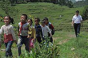 QIANNAN, CHINA - MAY 31: (CHINA OUT) <br /> <br /> Six-pupil School In Mountain Of Qiannan<br /> <br /> The only teacher Wu Guoxian and students go for a home visit on May 31, 2016 in Qiannan Buyei and Miao Autonomous Prefecture, Guizhou Province of China. Gugang primary school with only one teacher and six students was located in the mountain where the traffic was blocked in Qiannan. 50-year-old Wu Guoxian had been teaching in this school for 33 years and taught over 1,000 students. More and more people went out of the village to work in the cities leaving their children and the old in the mountain. Five under-school-age kids whose parents left for work also stayed at the school.<br /> ©Exclusivepix Media