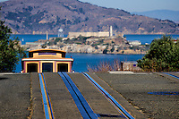Cable car rising over crest of a hill in San Francisco with Alcatraz Island in the background.