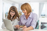 Cheerful mother and daughter shopping online at home during Christmas