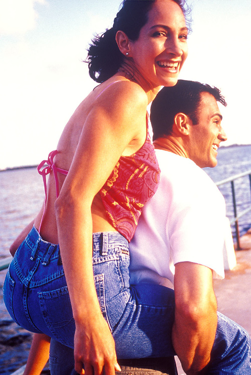Playful young couple, man carrying smiling woman.