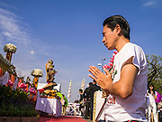 06 JANUARY 2013 - BANGKOK, THAILAND:  A man prays at a shrine in Bangkok during a service for a relic of the Buddha's hair. The relic has been on display in Bangkok for about 10 years. There was a ceremony in Sanam Luang in Bangkok Sunday to honor the relic. People prayed for it and received blessings from Buddhist monks and Brahmin priests who presided over the service. The hair is being moved to Ayutthaya, where it will be displayed in a Buddhist temple. The piece of hair has been on loan to Thai Buddhists from a Buddhist temple in Sri Lanka.   PHOTO BY JACK KURTZ