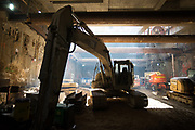 An excavator sits in silhouette inside the Chinatown Station headhouse, while workers waterproof the walls and install temporary steel supports.