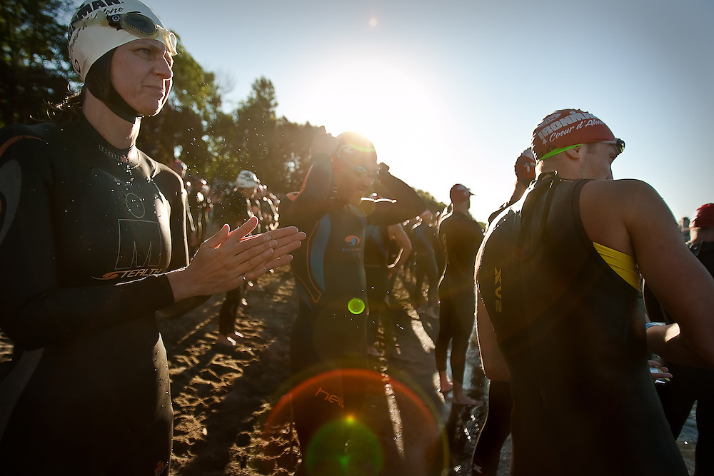 An Ironman hopeful eyes the swimming course just after the singing of the national anthem along the beach of Lake Coeur d'Alene on Sunday.