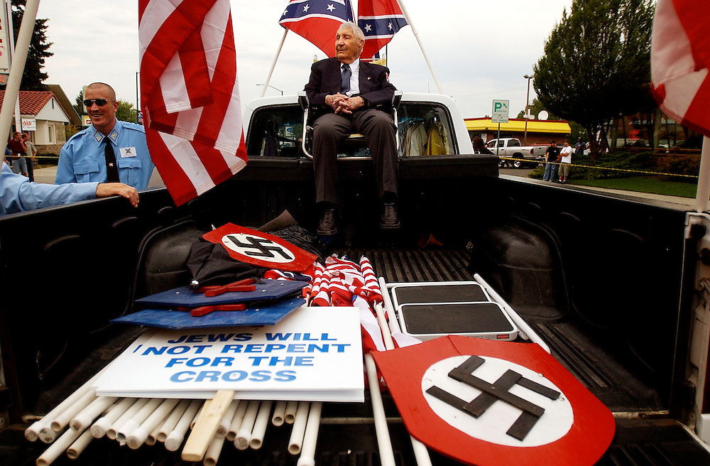 COEUR D ALENE, ID - JULY 17:  Rev. Richard Butler, leader of the Aryan Nations, sits in the back of a truck at the beginning of the World Congress Parade held in Coeur d'Alene, Idaho, on Saturday, July 17, 2004. About 40 supporters and members marched in downtown Coeur d'Alene for the Aryan World Congress.  (Photo by Jerome Pollos/Getty Images)