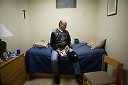 Feb.4 2014 - New York, NY. Peter Rivera, 53, is sitting on his bed, holding his favorite book. He's signed a six-month-program with the St. Anthony Shelter for Renewal in the South Bronx. 02/04/2014 Photograph by Qingqing Chen/NYCity Photo Wire