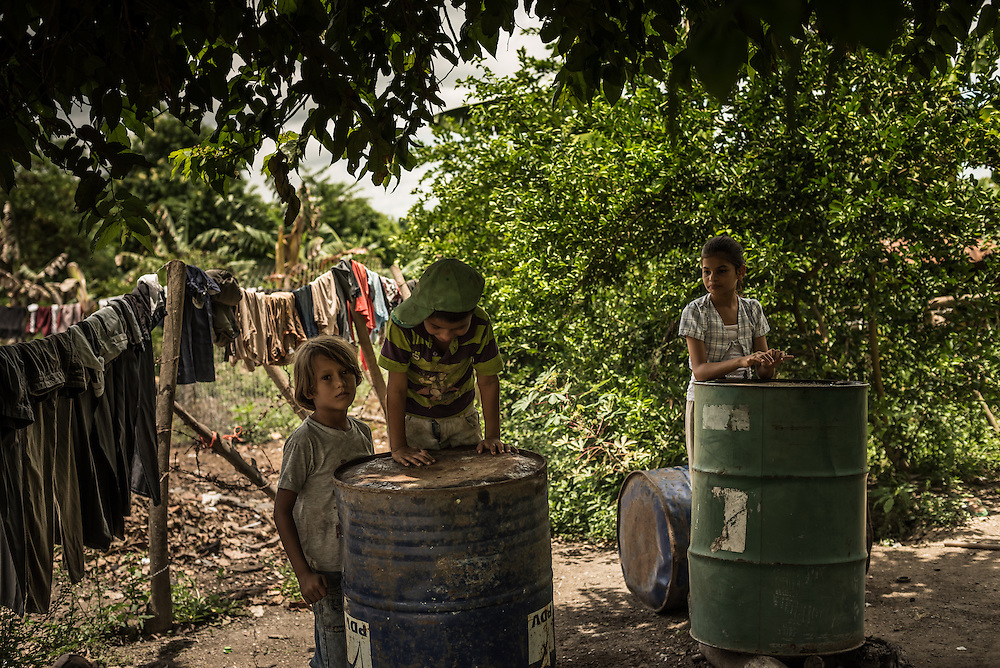 "BARALT MUNICIPALITY, VENEZUELA - AUGUST 28, 2014: Children play on old oil drums in the yard of their humble home, located close to oil wells in the Baralt municipality of Zulia state. However despite being so close to wells that have brought Venezuela tremendous oil wealth, the streets are unpaved and people live in shacks made from corrugated metal sheets. ""Look at the riches of Venezuela,"" said Ramón Materán, 64, a laborer. ""For all of Venezuela's riches things are pretty neglected here."""