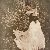 atmospheric photo of beautiful young caucasian woman looking aside in retro style in wedding dress standing in the woods holding of the tree