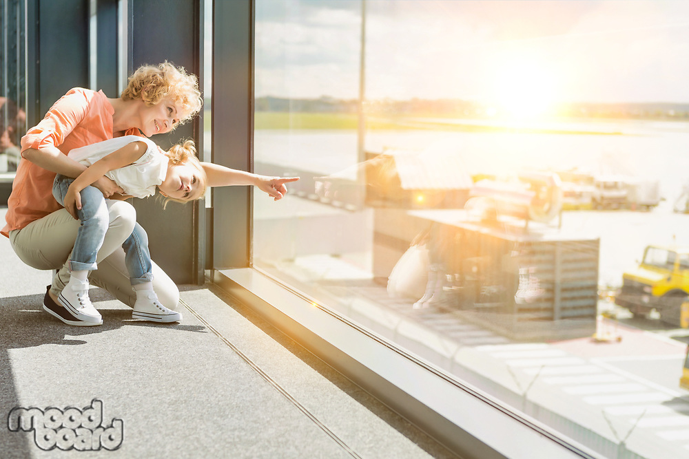 Portrait of mature woman with her cute little daughter looking throught the window in airport
