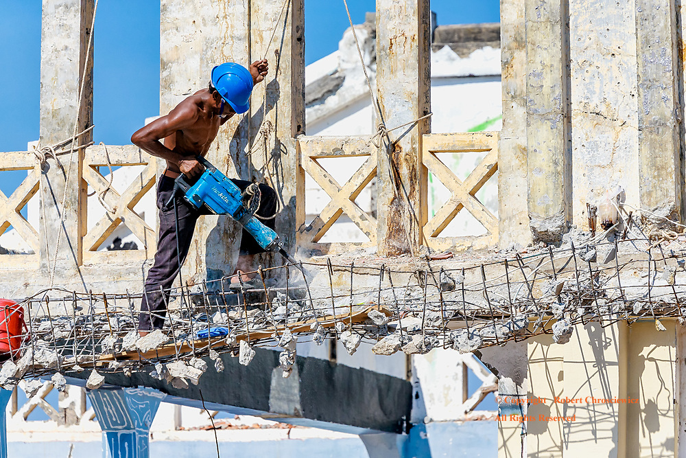 Safety?: A demolition worker is jack hammering concrete high on the exterior of a building, without the faintest consideration of safety precautions, Kampot Cambodia.