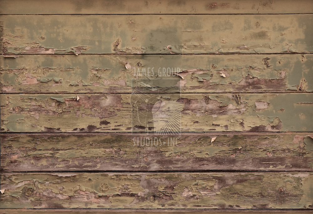 Distressed wood planks on an aged building showing blistered paint and wood grain
