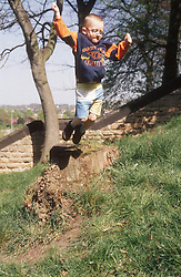 Young boy jumping off log in park,