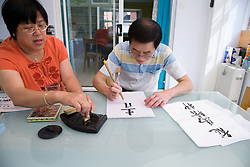Woman mixing ink on a block whilst husband does Chinese art writing,