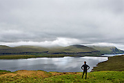 Eidisvatn Lake, Eysturoy Island, Faroe Islands.<br /> <br /> A man wearing sunglasses takes in the natural beauty of Eidisvatn (Eiðisvatn) Lake, which is dammed and a major supplier of electricity for the islands.