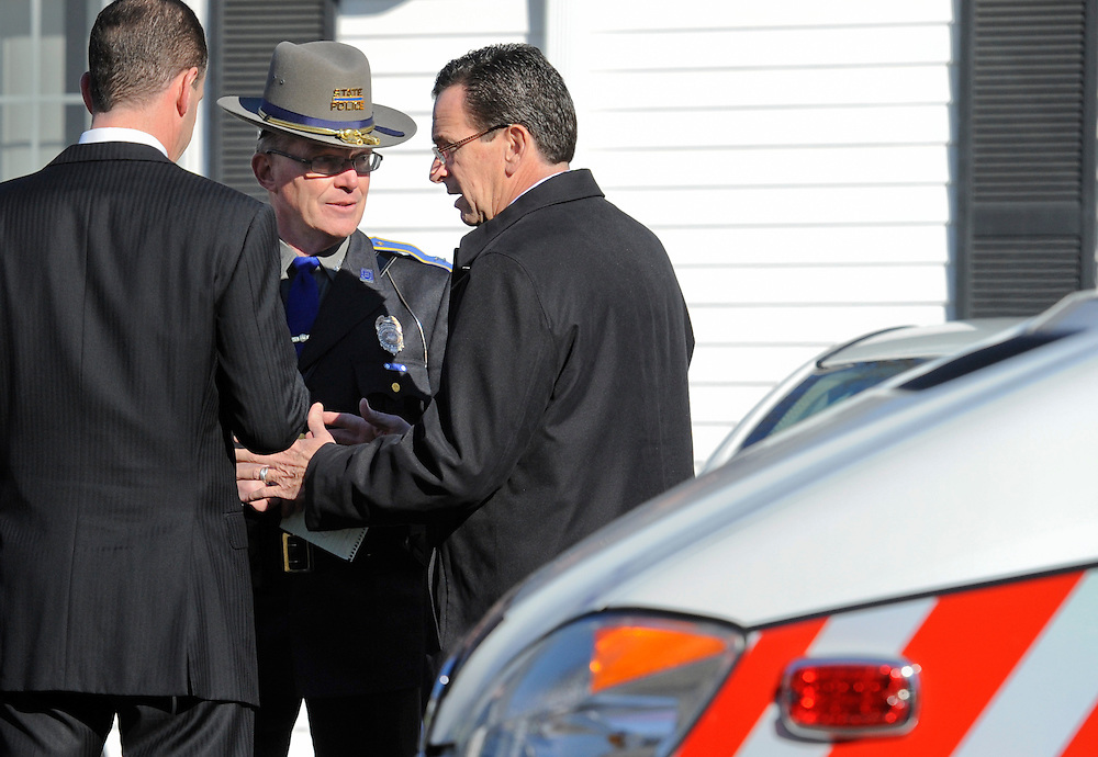 "Gov. Dannel P. Malloy, right, said early reports of the shooting suggested a domestic assault and that he only learned the scale of the crime on drive down to town.  Here he speaks with Colonel Danny R. Stebbins, Commander of the Connecticut State Police, center, and senior adviser Roy Occhiogrosso, left, outside a room where families have been waiting for several hours for information about their children. Malloy made the decision to tell the families their loved ones would not be returning shortly after this meeting.  He said afterward, ""It was evident to me that there was a reluctance to tell parents and loved ones ... that the person that they were waiting for was not going to return ... and that had gone on for a period of time, I made the decision that -- to have that go on any longer -- was wrong."" (AP Photo/Jessica Hill)"