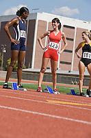 Female athletes next to starting blocks, chatting