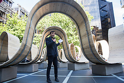 London, UK. 13 September, 2019. Artist Paul Cocksedge discusses his Please Be Seated installation in Finsbury Square Avenue in the heart of Broadgate. A Landmark Project for the London Design Festival made from scaffolding planks in collaboration with Essex interiors company White & White, the installation features curves for people to sit on and walk under and is intended to respond to the changing rhythm of the community, so enhancing London's largest pedestrianised neighbourhood.