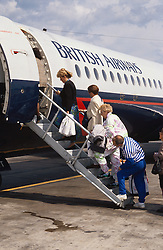 Passengers walking up steps to board aeroplane on airport runway,