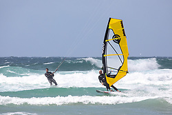 © Licensed to London News Pictures. 27/06/2020. Newquay, UK. A kitesurfer and a windsurfer enjoy windy weather at Watergate Bay, Cornwall. The weather is variable with sunny outbreaks and rainy showers. Photo credit : Tom Nicholson/LNP