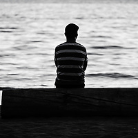 A lone man in a striped shirt sitting on a log staring out into the ocean