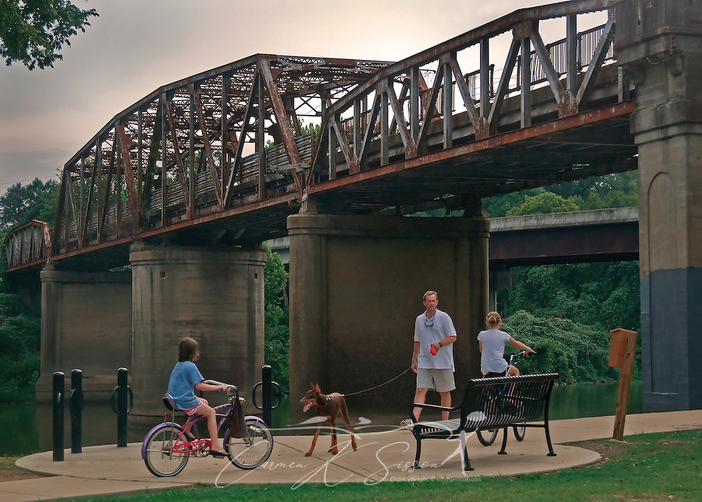 People walk and bicycle along the Columbus Riverwalk at Riverside Park in Columbus, Miss. Aug. 15, 2010. Plans are currently underway to restore the old Hwy. 82 bridge in the background. The bridge spans the Tennessee-Tombigbee Waterway and may eventually become a pedestrian walkway. (Photo by Carmen K. Sisson/Cloudybright)