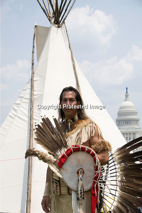 "A Lakota Brave/Warier/Native American Indian wearing native dress and war shield with a Tee-Pee and US Capital in the background at the 2008 ""The Longest Walk 2"" rally at The National Mall near The American Indian Museum in Washington D C."