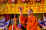 "09 AUGUST 2014 - BANGKOK, THAILAND:  A Vietnamese Mahayana Buddhist monk throws candies to the crowd during a Ghost Month service at the Ruby Goddess Shrine in the Dusit section of Bangkok. The seventh month of the Chinese Lunar calendar is called ""Ghost Month"" during which ghosts and spirits, including those of the deceased ancestors, come out from the lower realm. It is common for Chinese people to make merit during the month by burning ""hell money"" and presenting food to the ghosts. At Chinese temples in Thailand, it is also customary to give food to the poorer people in the community.        PHOTO BY JACK KURTZ"