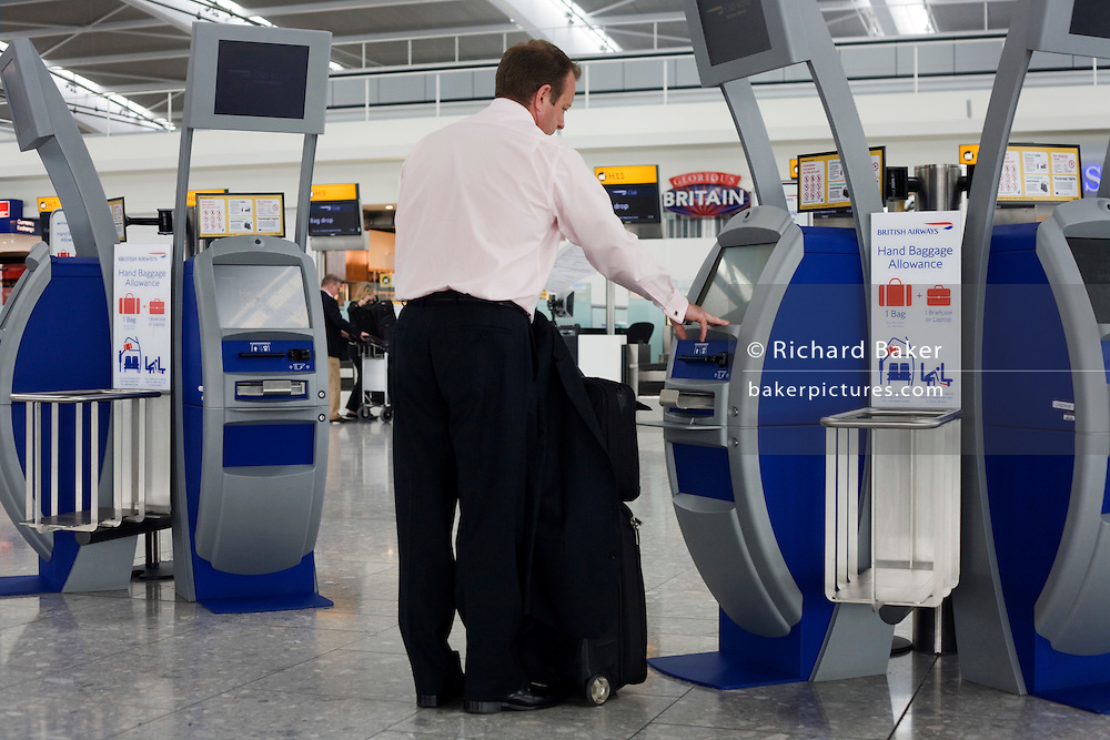 Departing passenger use British Airways self-service check-in kiosks at Heathrow Airport's Terminal 5.