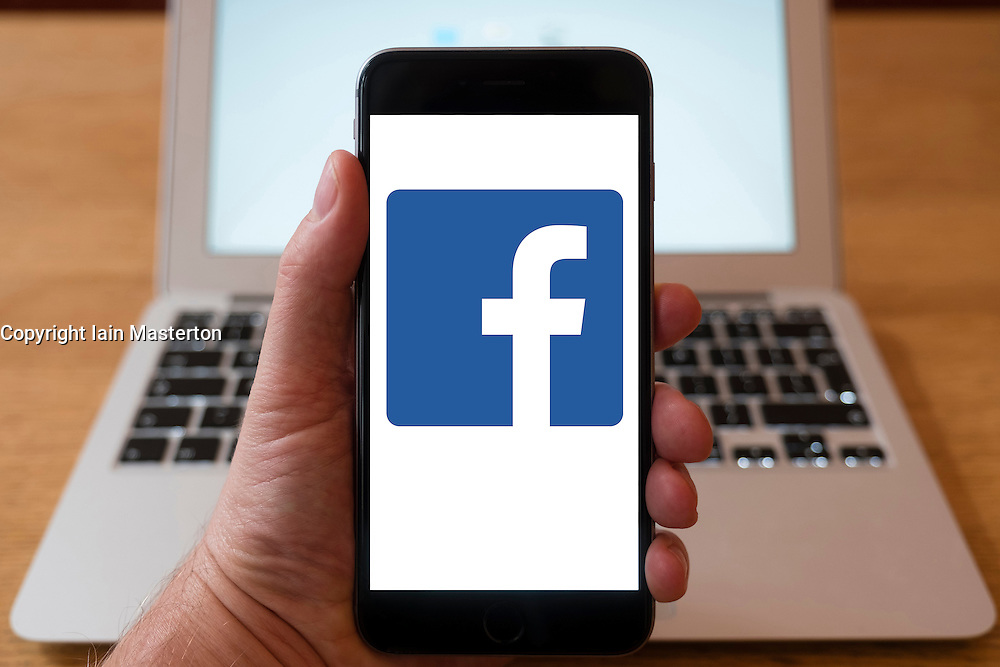 Using iPhone smartphone to display logo of Facebook social media website