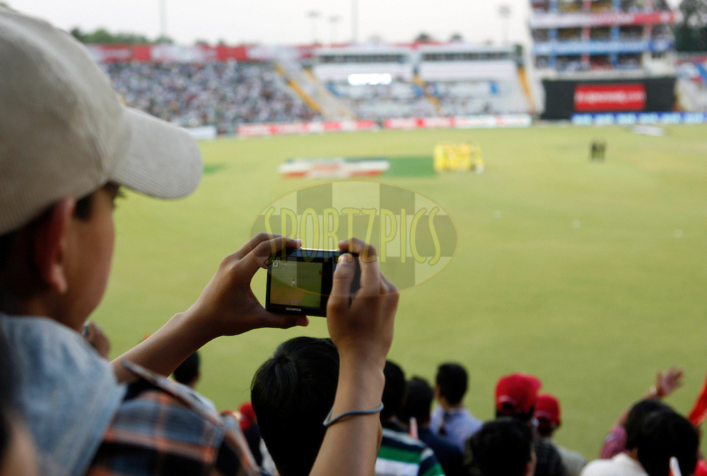 A child clicks picture sitting inside the stadium during match 9 of the Indian Premier League ( IPL ) Season 4 between the Kings XI Punjab and the Chennai Super Kings held at the PCA stadium in Mohali, Chandigarh, India on the 13th April 2011..Photo by Money Sharma/BCCI/SPORTZPICS